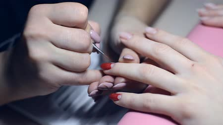 Manicurist paints nails with red lacquer in the salon Stock Footage