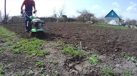 akkerland : Cultivates the ground in a garden with a tiller, preparing the soil for sowing