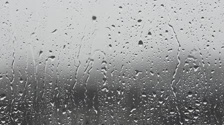 Rainy day, raindrops dripping on the window glass