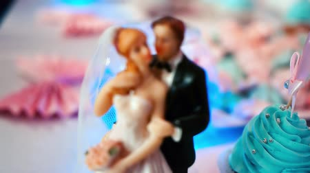wedding cake : Bride and groom figures on wedding cake on blinking background. Stock Footage