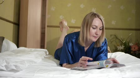 časopis : Beautiful blonde girl lying on the bed and reading a magazine