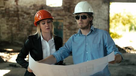 planları : architect builder engineer builder of ruined building looking girl work plan for the construction site construction plan explains in helmet construction helmet girl looks architectural plan and construction plans to repair the area Stok Video