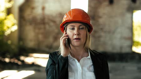 проект : architect builder engineer builder of ruined building looking girl work plan for the construction site construction plan explains in helmet construction helmet girl looks architectural plan and construction plans to repair the area Стоковые видеозаписи