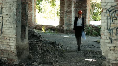 projects : architect builder engineer builder of ruined building looking girl work plan for the construction site construction plan explains in helmet construction helmet girl looks architectural plan and construction plans to repair the area Stock Footage