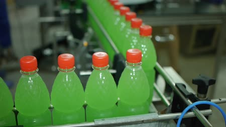 production tool : bottles move along the production line lemonade soda mineral water are filled and packaged Stock Footage