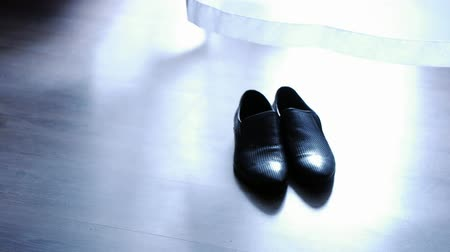 couro : Mens shoes are on the floor next to the curtain, mens accessories