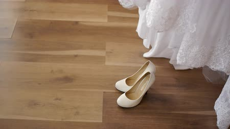 high heeled sandals : brides dress with shoes standing on the floor