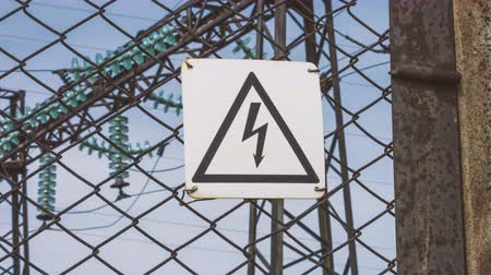płot : The danger sign of high voltage on the fence of the power plant. Risk of electric shock. Power generators, electricity generation and transportation to cities. Power engineering. Stand - high voltage. a warning. Wideo