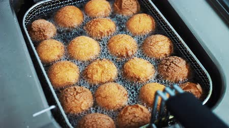 kızartma : Preparation of donuts in hot oil in the deep fryer. Boiling oil with donuts close-up. The cook is preparing food. Stok Video