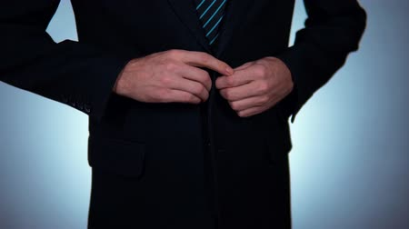 buttoning : slow motion, businessman buttoning his jacket.
