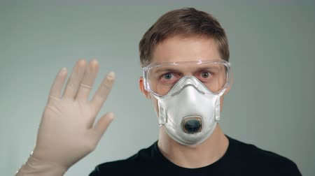 influenza background : protective mask on the face of a man. waving his hand in the glove. medicine, polluted atmosphere, respiratory and eye protection. Stock Footage