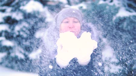 hófúvás : girl blowing snow in a winter park, smiling and enjoying the snow, slow motion
