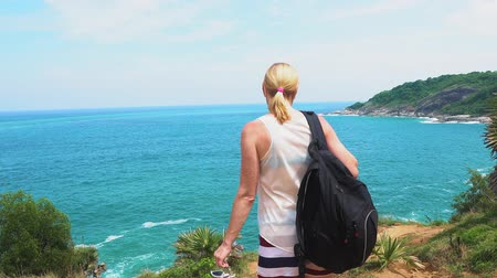 лодки : traveler girl looks at a beautiful seascape on the edge of a cliff Стоковые видеозаписи