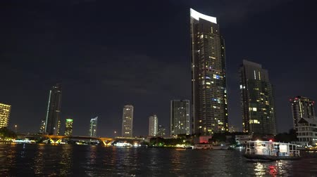 megalopolis : corporate buildings on the river bank with offices. night time in the big city, light from the windows of business centers.