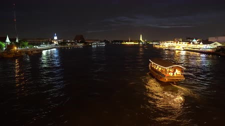 keresztül : Big cruise boat with illuminated colorful lights sailing across the river at night along cityscape Stock mozgókép