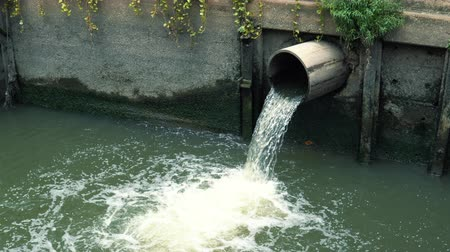 kanalizace : Drain polluted water through sewage into the canal at city street, side view