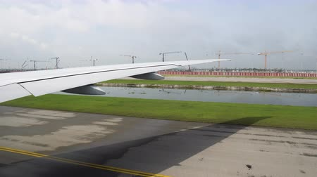 the plane on the runway preparing to take off. view of the wing of the aircraft from the window Стоковые видеозаписи