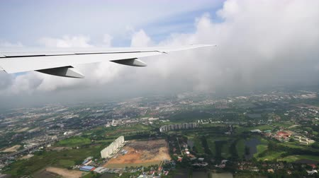 The ground is visible under the wing of aircraft. The plane flies over the city and green fields Стоковые видеозаписи