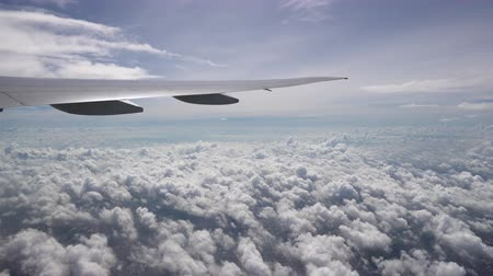 The wing of aircraft moves over the white Cumulus clouds. Sunlight and clear blue sky on the skyline Стоковые видеозаписи