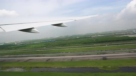 The wing of aircraft over the runway. The plane moves through the airport