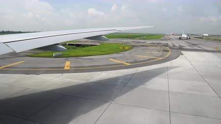 The runway under wing of aircraft. Airplane moving on the runway in terminal of departure in the airport