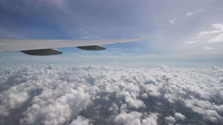 The plane flies high above the clouds and ground. The wing of aircraft in blue sky at the horizon Стоковые видеозаписи