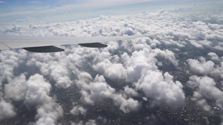 The wing of airplane over the white fluffy clouds. The earth is seen under the wing of aircraft Стоковые видеозаписи