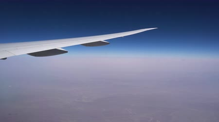 Flying at high altitude. The wing of aircraft on the background of clear sky and endless horizon Стоковые видеозаписи
