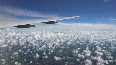 The plane flies in the blue sky. White clouds and city below under the wing of aircraft
