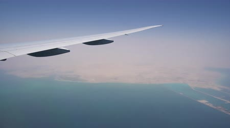 the plane flies over the sea water. visible coastline from the window. air transportation and travel
