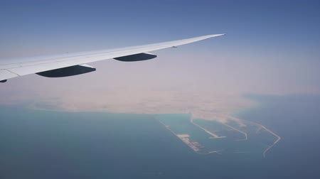 the plane flies at high altitude. view from the window on the wing. turquoise water under the wing of the aircraft