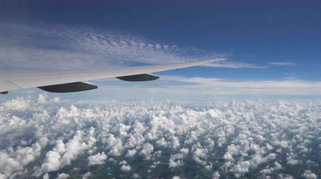 The wing of a passenger plane through the window. Serene view of the skyline with clouds
