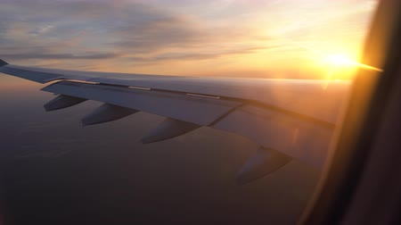 sunset in the window of the plane. beautiful view of the aircraft wing. passenger transportation and travel Стоковые видеозаписи