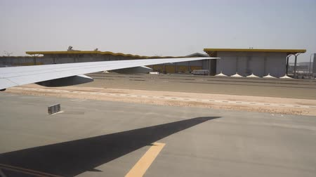 Large aircraft wing over the runway on a hot Sunny day