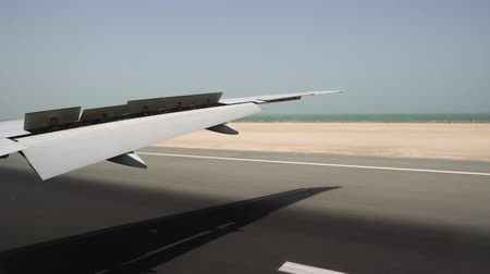 The aircraft landing on the runway. View from the window on the big plane wing and the ocean on the horizon