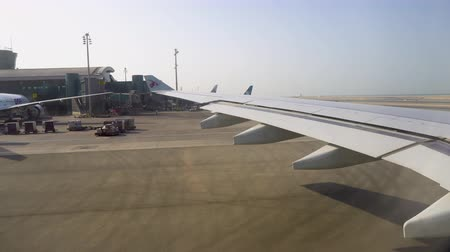 the plane is waiting for departure at the international airport. view from the window of the aircraft on the wing and terminals Стоковые видеозаписи