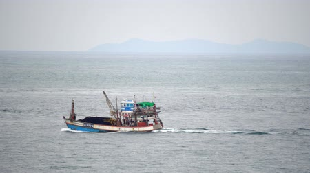 ryba : Fishing boat sails into the sea for seafood on a cloudy day