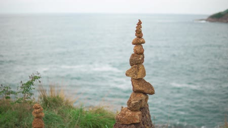 стабильность : A cairn is stands on top of a cliff against the blue sea. Heap of stones close-up