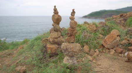 stacked rock : Two pyramids of stones stands on the sandy ground. Cairn on the hilltop above the sea