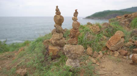 мифический : Two cairn standing up on the high rock.  Heap of stones at the sea background
