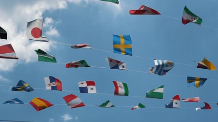 глянцевый : Slow motion, group of nationals flags at blue sky with white clouds. Flags of many countries of the world in the air