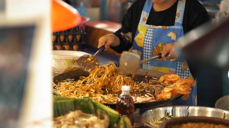 vegetable wok : Cooking a delicious Pad Thai on a large wok, slow motion. Chef cooking the asian street food at night market