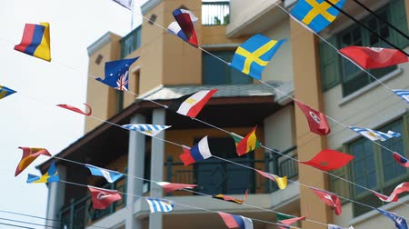 asma : Slow motion, flags suspended on thin rope in the air above the street. Symbols of different nations waving in the wind