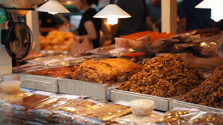 exotic dishes : Asian night food market, slow motion. Large dishes with a variety of traditional meals are laid out on the stall