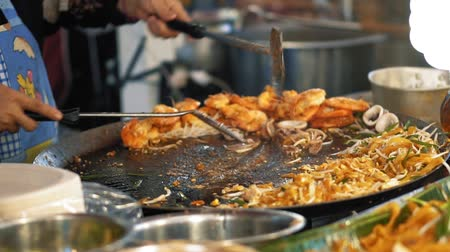 саженцы : Preparation fresh delicious food at the night market, slow motion. Chef roasts seafood in a hot pan on the street