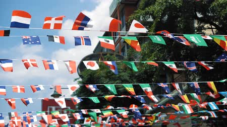 atributo : Various national flags waving in the air at the sunny day. Flags as attribute of world event