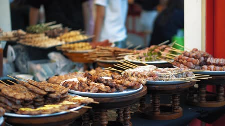 prodávat : Traditional Asian food is sold at the night market in Thailand. Fried chicken pieces, sausages, bacon are appetizing on the plates
