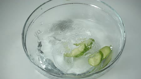 picado : Fresh cucumber slices falls into a glass bowl with water standing on the table, slow motion Stock Footage