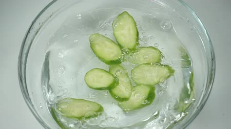 pepino : Cucumber slices in a glass bowl of water on kitchen, slow motion. Clean water splashes from fresh cucumber pieces falling