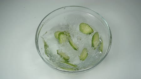 pepino : Slices of fresh cucumber fall into a glass dish of water, slow motion. A few slices of green cucumber floating in the clear water